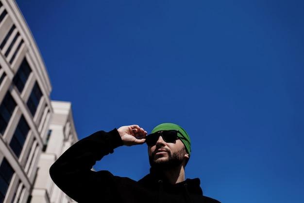 ファッショナブルなハンサムな男は、青い空を背景にサングラスをかけています。コピースペース