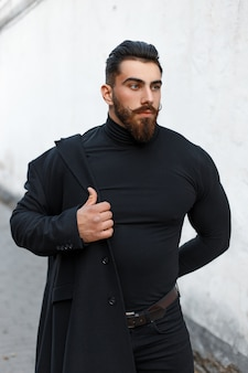 Fashionable handsome man with a hairdo and a beard puts on a black stylish coat on the street