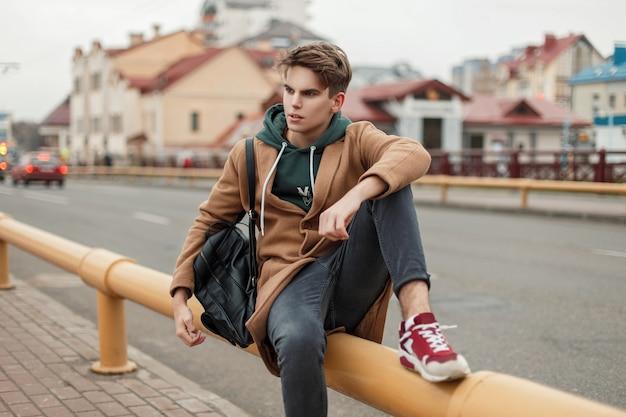 검은 가죽 가방과 스니커즈가 도시의 파이프에 앉아있는 까마귀가있는 빈티지 세련된 코트의 이발이있는 세련된 잘 생긴 모델 남자