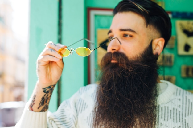 Fashionable handsome young bearded man holding yellow eyeglasses in hand