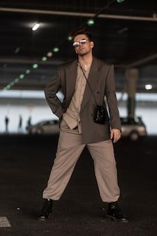 サングラスとハンドバッグとファッショングレーのスーツを着たファッショナブルなハンサムな若いクールな男が駐車場に立っています