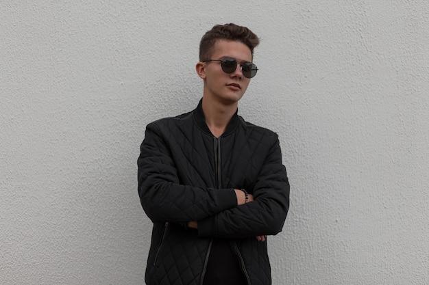 검은 세련된 옷을 입고 유행 잘 생긴 젊은 남자가 회색 벽 근처에 선다.
