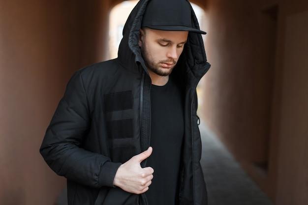 거리에서 겨울 재킷과 후드에 검은 야구 모자와 유행 잘 생긴 젊은 남자