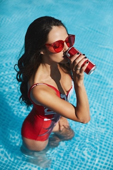 Fashionable and happy brunette model woman with a perfect sexy figure in stylish red swimsuit and trendy red sunglasses in the swimming pool drinking a cold drink