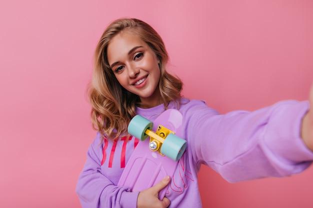Модная счастливая девушка со скейтбордом, делая селфи. беззаботная кудрявая дама фотографирует себя на розовом.