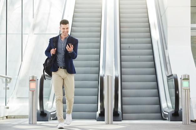 Fashionable happy man on telephone call by escalator