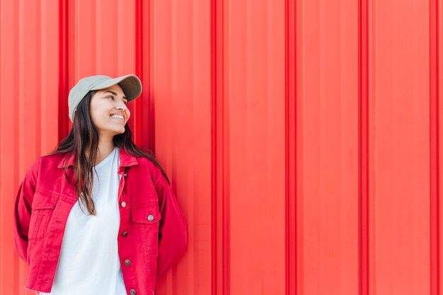 Fashionable happy woman looking away against red background