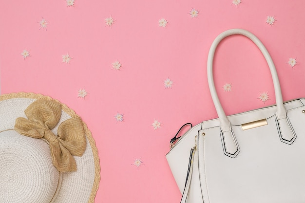 花とピンクの背景にファッショナブルな帽子と白いバッグ。女性のためのファッショナブルな服やアクセサリー。フラットレイ。