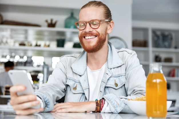 Fashionable hipster guy dressed in denim shirt and wearing stylish glasses