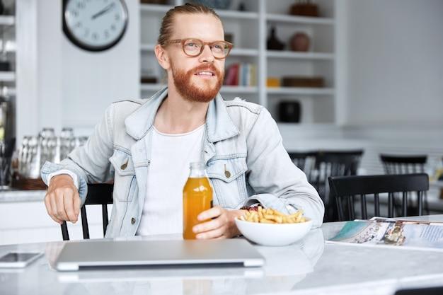 Модный хипстерский парень в джинсовой рубашке и стильных очках