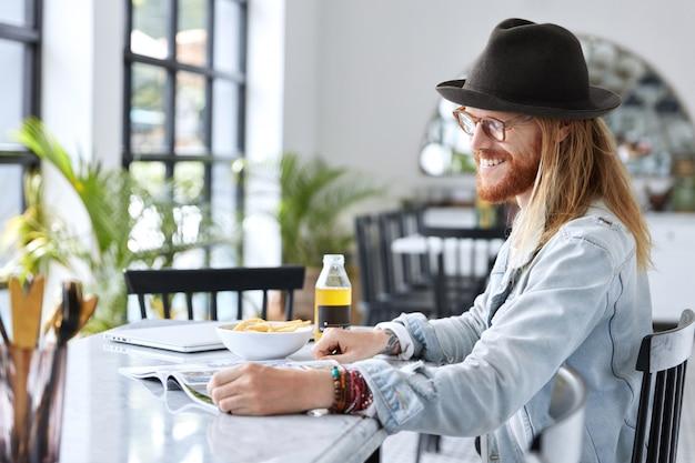 Модный хипстерский парень, одетый в стильную черную шляпу и джинсовую рубашку