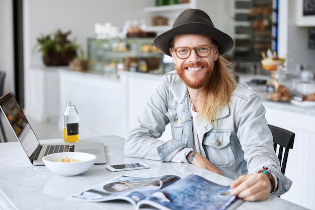 Fashionable hipster guy dressed in stylish black hat and denim shirt