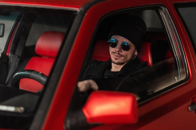 파란색 선글라스와 모자를 쓴 세련된 힙스터 남자는 오래된 빨간 차의 바퀴 뒤에 앉습니다. 남자 택시 운전사