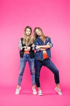 Fashionable hipster sisters in jeans posing with crossed arms.