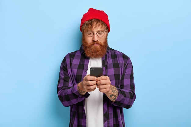 Fashionable hipster with red hair and thick beard, focused in smart phone, recieves link to some publication