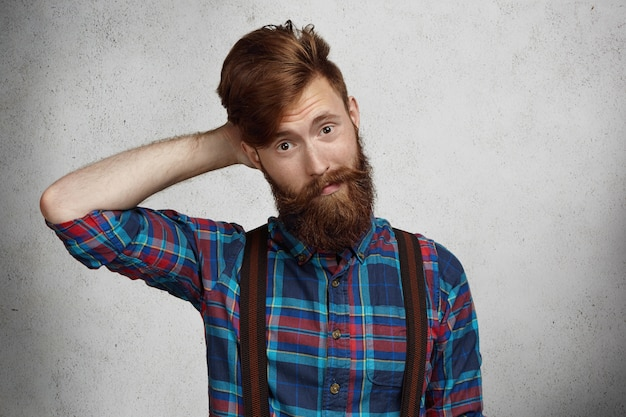 Fashionable hipster with thick beard dressed in trendy checkered shirt and suspenders looking puzzled and confused, holding hand behind his head.