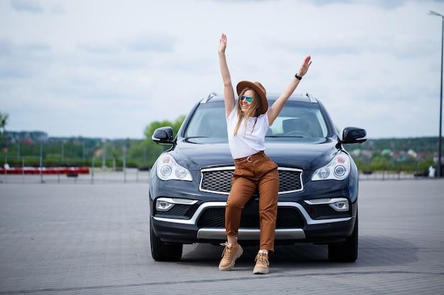 Модный образ стильной молодой девушки в шляпе и белой футболке. девушка стоит возле черной машины с улыбкой на лице