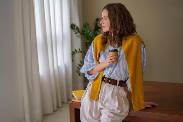 彼女の朝のコーヒーのカップを保持し、オフィスでポーズをとって若いブルネットの女性のファッショナブルなイメージ