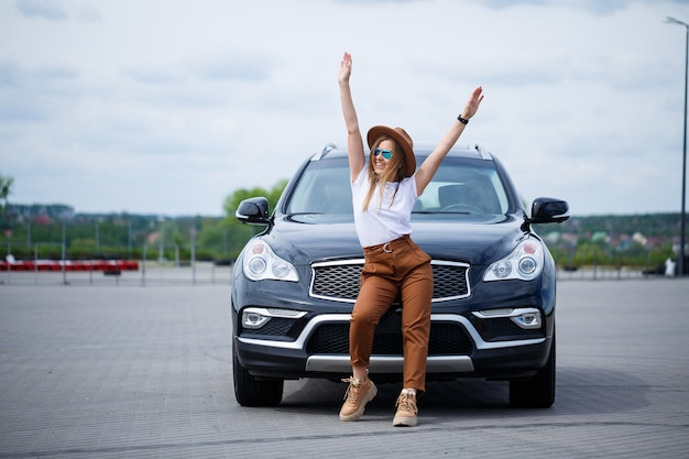 Fashionable image of a stylish young girl in a hat and white t-shirt. a girl stands near a black car with a smile on her face