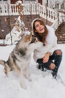 Giovane donna allegra alla moda che si diverte con il cane husky adorabile nella neve sulla strada. vere emozioni, momenti felici nel periodo invernale, sorridere, esprimere positività.
