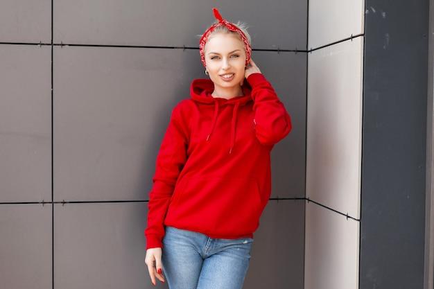 빨간 두건과 현대적인 유행의 옷에 귀여운 미소로 유행 즐거운 젊은 여자가 따뜻한 여름날에 회색 빈티지 건물 근처에 서있다