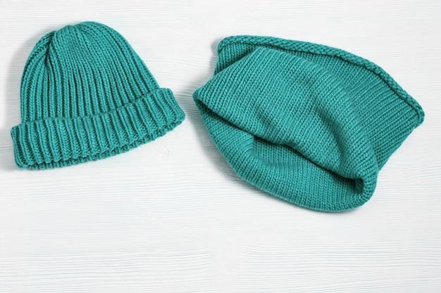 Модная вязаная одежда ярких оранжевых цветов теплая шапка уютный мягкий шарф снуд на белом деревянном
