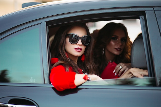 Fashionable ladies in the car. portrait of stylish gorgeous ladies in sunglasses