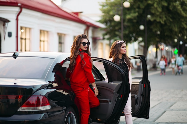 Fashionable ladies going out of the car.