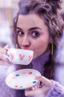 ファッショナブルな女性。水彩画のプリントでカップからお茶をすすりながら大きな茶色の目を持つ魅力的な黒髪の女性