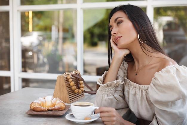 カフェでファッショナブルな女性、コーヒーを飲み、テーブルに寄りかかって、屋外の景色を楽しんでいます。