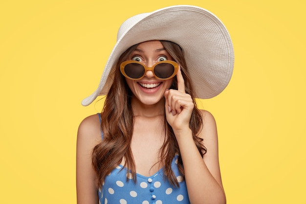 Fashionable lady with glad expression, wears white hat and sunglasses, finds hotel to stay during vacation, ready to go on beach, isolated over yellow wall. tourism and summer time concept