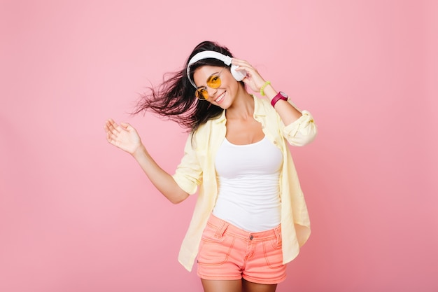 Fashionable latin girl in good mood posing for photo and dancing. enthusiastic hispanic young lady in summer outfit relaxing while listening favorite song.