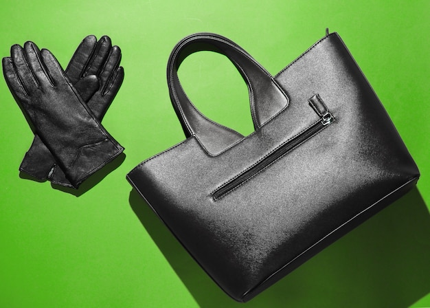 ファッショナブルな革のバッグ、緑の背景に手袋。上面図、ミニマリズム