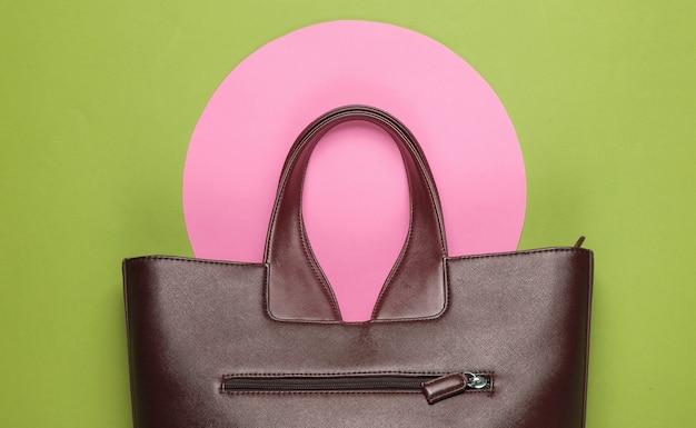 Модная кожаная сумка на зеленом фоне с розовым пастельным кругом. вид сверху