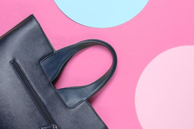 Модная кожаная сумка на розовом фоне с голубыми и розовыми пастельными кругами. вид сверху