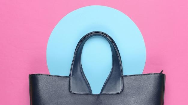 Модная кожаная сумка на розовом фоне с голубым пастельным кругом. вид сверху