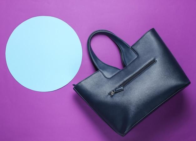 Модная кожаная сумка на фиолетовом фоне с голубым пастельным кругом для копирования пространства.