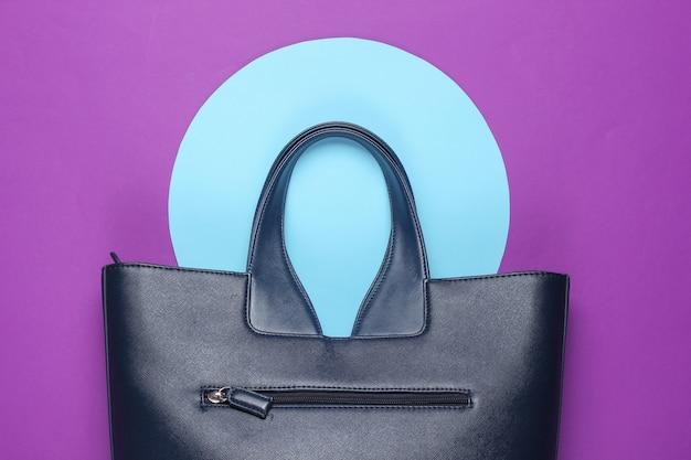 青いパステルサークルと紫の背景にファッショナブルな革のバッグ。