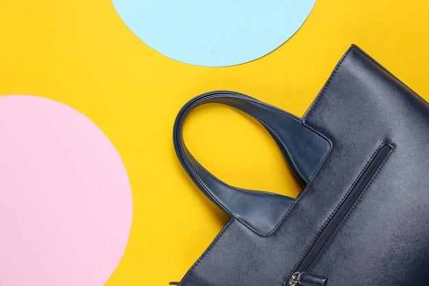 青とピンクのパステルサークルと黄色の背景にファッショナブルな革のバッグ。上面図