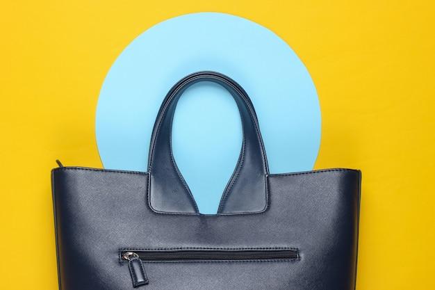青いパステルサークルと黄色の背景にファッショナブルな革のバッグ。上面図