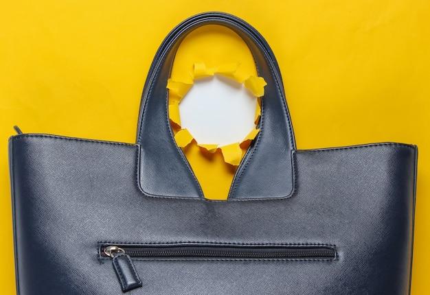 引き裂かれた穴と黄色の背景にファッショナブルな革のバッグ。上面図