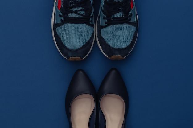 クラシックなブルーの背景にファッショナブルな革のハイヒールの靴とスポーツスニーカー。カラー2020。上面図。