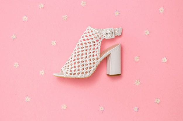 花とピンクの背景にファッショナブルな革の靴。女性のための夏の靴。フラットレイ。上からの眺め。