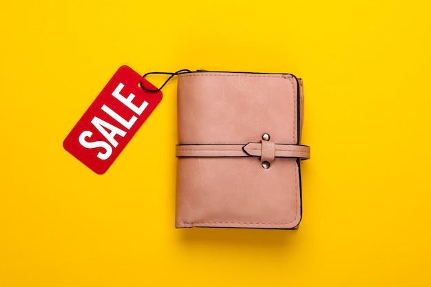Модный кожаный кошелек с красной биркой на желтом .. скидка. покупка. минимализм