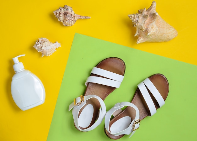 Fashionable leather women's sandals, seashells, sunblock on colored pastel surface, top view, flat lay