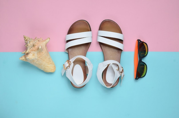 Fashionable leather women's sandals, seashells, sunglasses on a colored pastel surface, top view, flat lay
