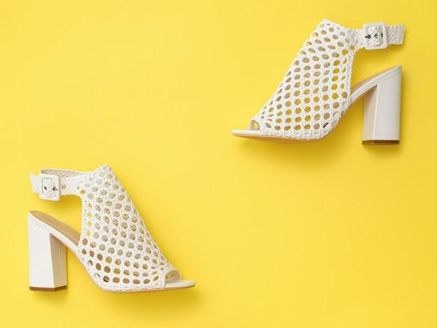 黄色の背景に斜めに配置されたファッショナブルな革の女性の靴。女性のための夏の靴。フラットレイ。上からの眺め。