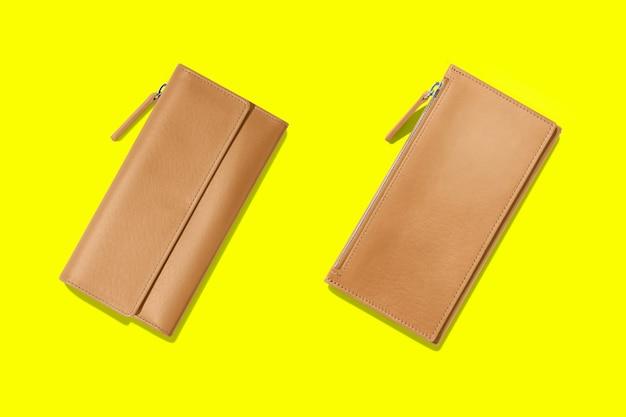 Модные кожаные женские кошельки на желтом фоне. добавлено место для копирования текста.
