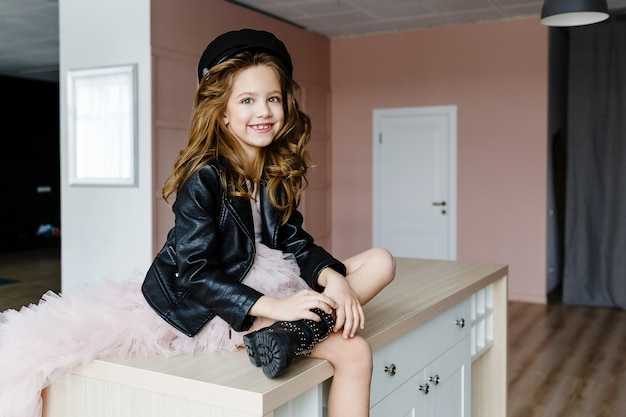 Fashionable little girl in a pink dress and black leather jacket