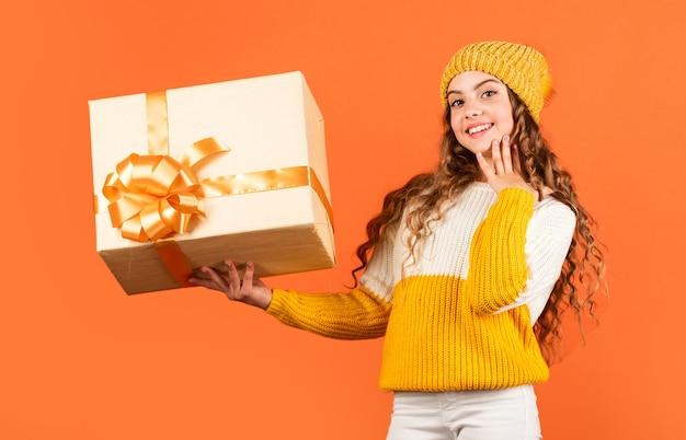 유행 어린 소녀는 니트 모자와 스웨터를 입는다. 생일 깜짝. 생일 전통. 예쁜 십 대 메이크업 얼굴 곱슬 헤어스타일입니다. 아이 보유 선물 상자. 쇼핑몰. 생일 축하 아이디어.